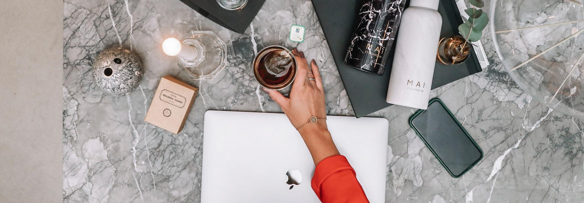 Hand som sträcker över dator mot kaffekopp
