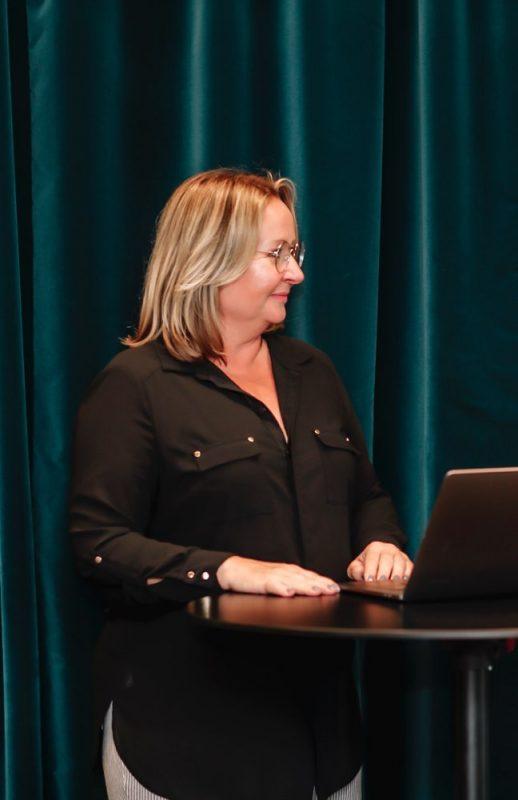Kvinna som står vid en dator
