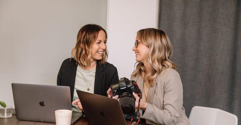 Två personer som sitter vända mot varandra och pratar framför en datorskärm