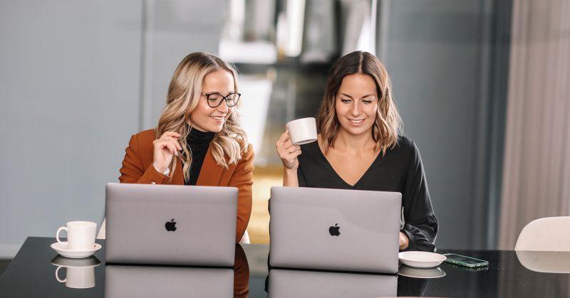 Två tjejer som sitter vid laptops och dricker kaffe